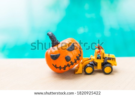 Halloween pumpkin with blurred yellow truck and a worker over blurred blue water background, truck moving pumpking time for celebrate halloween, outdoor day light #1820925422