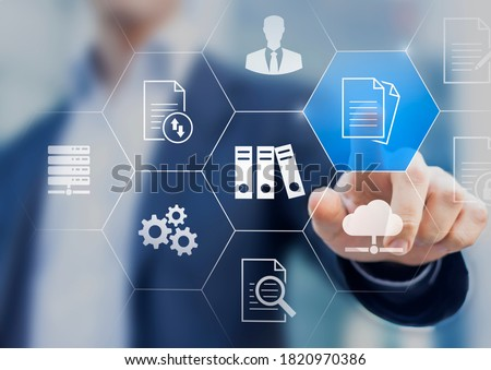 Document Management System (DMS) used to store, search and manage review process and users for corporate files and information in enterprise. Concept with business manager pointing to icons. #1820970386