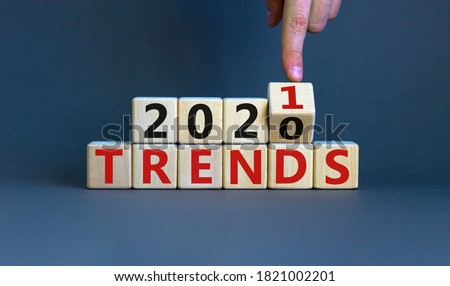 Business concept of planning 2021. Male hand flips wooden cube and change the inscription 'TRENDS 2020' to 'TRENDS 2021'. Beautiful grey background, copy space. Royalty-Free Stock Photo #1821002201