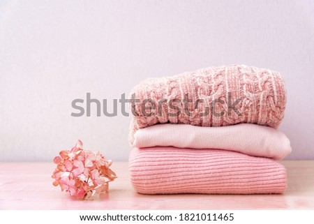 Stack of folded wool knitted sweaters or pullovers in pink pastel colors on table with flower hydrangea. Close up of warm cozy comfortable monochrome clothes for autumn winter season. Royalty-Free Stock Photo #1821011465