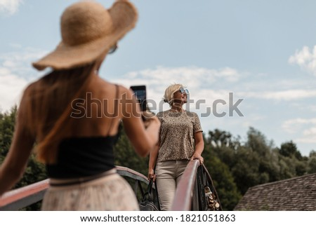 Young daughter taking pictures of fashionable mother in leopard print t-shirt with sunglasses on the phone, family trip