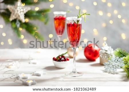 Mimosa festive drink for Christmas - champagne red cocktail Mimosa with cranberry for Christmas party, copy space and fir tree branches #1821062489