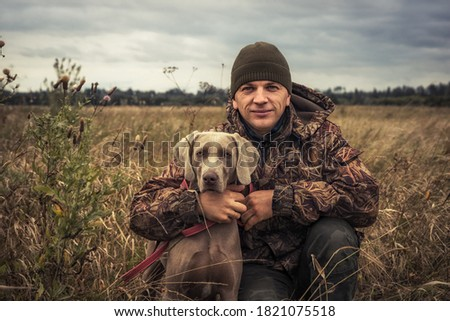 Man hunter with hunting dog Weimaraner friend portrait in rural field during hunting season Royalty-Free Stock Photo #1821075518