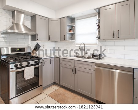 a small modern kitchen with grey cabinets Royalty-Free Stock Photo #1821123941