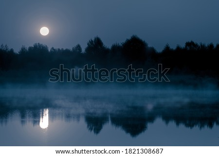Night mystical scenery. Full moon over the foggy river and its reflection in the still water. Royalty-Free Stock Photo #1821308687