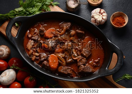 Beef Bourguignon in a pan. Stew with red wine ,carrots, onions, garlic, a bouquet garni, and garnished with pearl onions, mushrooms and bacon. French cuisine- regional recipe from Burgundy #1821325352
