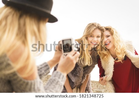 Three females friends having fun during outdoor photo session. Woman taking pictures of two during warm autumn weather.
