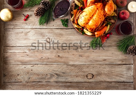 Roasted Christmas Chicken or Turkey for Christmas Dinner. Festive decorated wooden table for Christmas Dinner with baked chicken, top view, copy space. #1821355229
