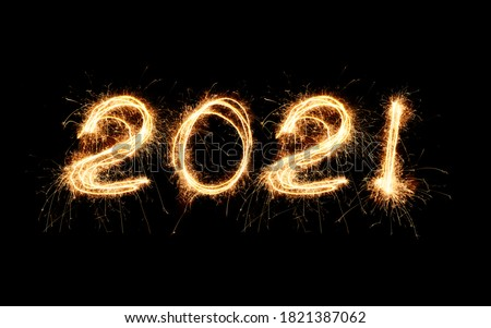 New Year 2021 light. Sparklers draw figures 2021. Bengal lights and letter Royalty-Free Stock Photo #1821387062