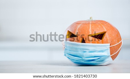 Celebration of halloween with medical mask concept. Pumpkin with a mask in white kitchen