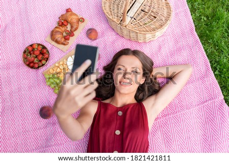 leisure and people concept - happy smiling woman with smartphone on selfie stick and picnic basket lying on blanket and taking picture at summer park