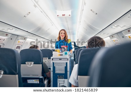 Interior of international airplane with passengers on seats and stewardess in uniform walking the aisle #1821465839