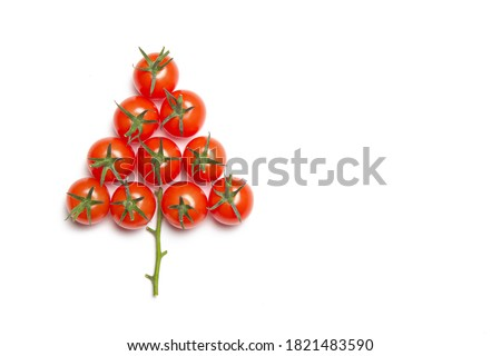 Christmas tree made of cherry tomatoes on a white background. Isolated background. Christmas decoration. Food tree. New year and Christmas. Seasonal holiday. Decoration of new year's window displays