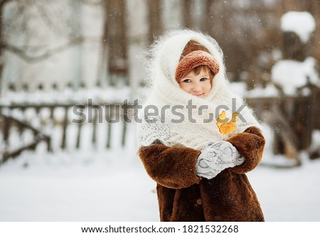 A little girl stands on the street in winter and holds a lollipop in her hands. A girl in a brown fur coat, mittens and a white downy knitted shawl. It's snowing outside. Winter photo session.