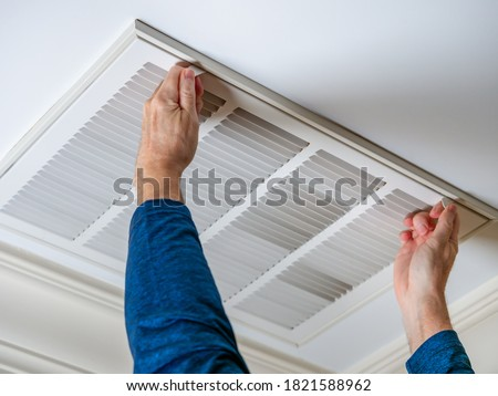 Man opening ceiling air vent to replace dirty HVAC air filter. Home air duct system maintenance for clean air. #1821588962