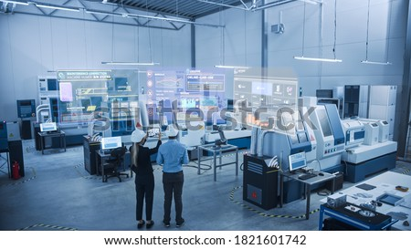 Industry 4.0 Factory: Two Engineers Uses Digital Tablet Computer with Augmented Reality Software to Connect with High-Tech Machinery, Robot Arm and Visualize Maintenance and Diagnostics of Equipment Royalty-Free Stock Photo #1821601742
