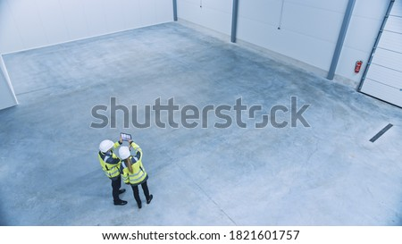 Industry 4.0 Modern Factory: Two Engineers in Empty Warehouse Use Digital Tablet Computer with Augmented Reality Software For a Room Mapping. Doing 3D Factory Floor Layout. High Angle Shot Royalty-Free Stock Photo #1821601757