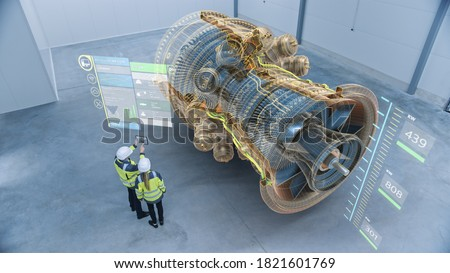 Industry 4.0 Two Engineers Standing and Talking in Factory Workshop with Augmented Reality 3D Model Concept of Giant Turbine Engine. Graphics Visualization. High Angle Shot. VFX Special Visual Effects Royalty-Free Stock Photo #1821601769
