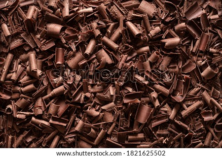 Chopped chocolate background. Flat lay of milk chocolate shavings. Close-up of baking chocolate texture. #1821625502