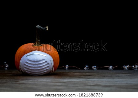Halloween Pumpkin on wood board with medical mask dark background copy space