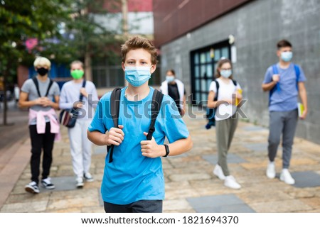 Portrait of teenager in protective mask with backpack going to school lessons on sunny autumn day. New lifestyle during coronavirus pandemic Royalty-Free Stock Photo #1821694370