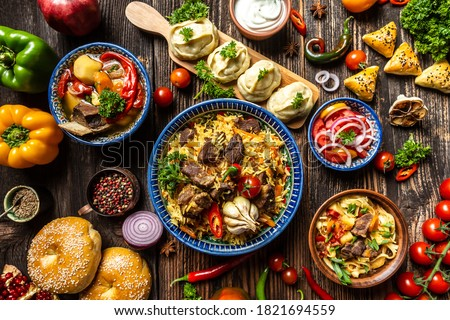 Uzbek and Central Asia cuisine concept. Assorted Uzbek food pilaf samsa lagman manti shurpa Uzbek restaurant concept Uzbek food. Food recipe background Royalty-Free Stock Photo #1821694559