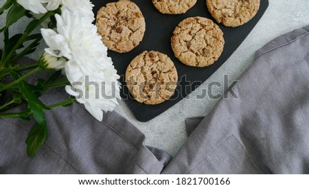 Flatlay picture of chocolate chip cookies on black wooden cutting board with flowers on white background