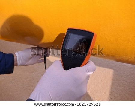 Measuring the thickness of the paint on the gas pipeline with the device. The worker controls the thickness and quality of the protective coating. Royalty-Free Stock Photo #1821729521