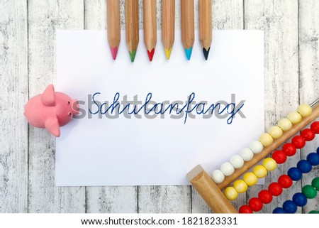 "School concept and template. Paper with handwriting ""Schulanfang"", frame with colored pencils, school supplies, slide rule, eraser, wooden background #1821823331"