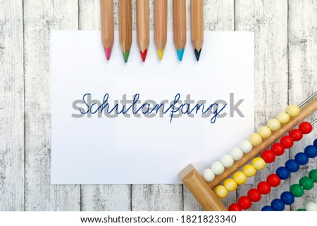"School concept and template. Paper with handwriting ""Schulanfang"", frame with colored pencils, school supplies, slide rule, eraser, wooden background #1821823340"