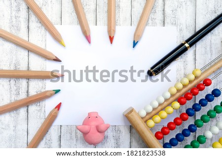 School and back to school concept and template. Blank paper and frame with colorful pencils, school supplies, slide rule, eraser, wooden background #1821823538