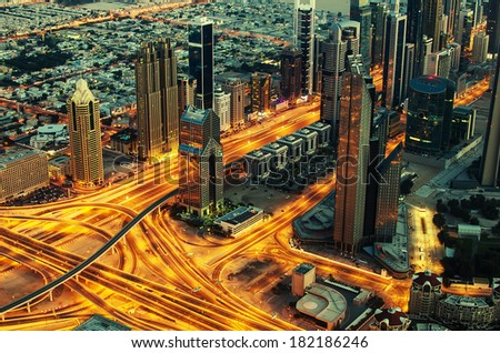 The United Arab Emirates, UAE: Downtown Dubai at night. View from Burj Khalifa, the tallest building in world. Aerial photo of futuristic cityscape in Arabian Peninsula. Golden lines of modern streets