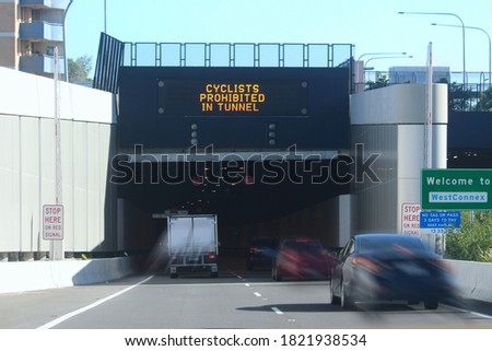 Cars and a truck entering the new M4 Westconnex tunnel at Ashfield from Parramatta Road. There is signage over the entrance reading 'Cyclists Prohibited in Tunnel. Speed limit is 60 km per hour