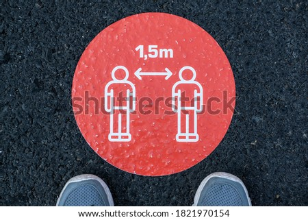 A circle floor sign with symbols of two people and lettering saying 1.5 meters. ensure social distancing on a tiled floor. Image