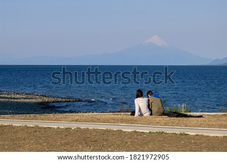 Back view of a couple sitting on the lake side. Far distance is a snow capped vacano. #1821972905