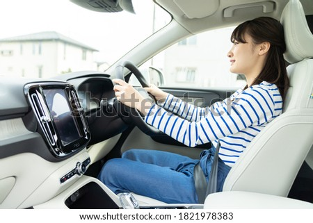 Young asian woman driving a car. Royalty-Free Stock Photo #1821978383