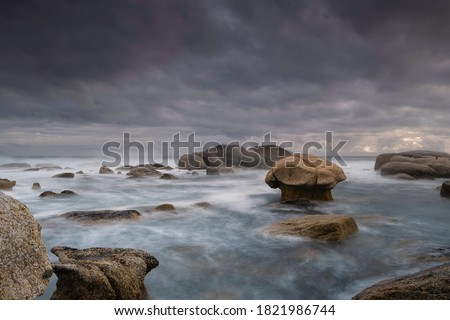 A stormy scene unfolds as the Atlantic Ocean meets the shoreline at the Cape of Good Hope and the turbulent waves rush towards the mushroom shaped rock in a slow motion long exposure landscape scene Royalty-Free Stock Photo #1821986744