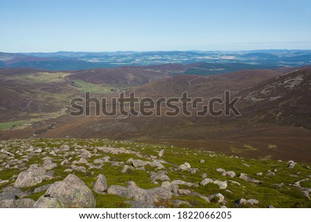 From the rocky summit of Mount Keen there is an elevated view of Glen Tanar and the green foothills of the Scottish Highlands beyond. #1822066205