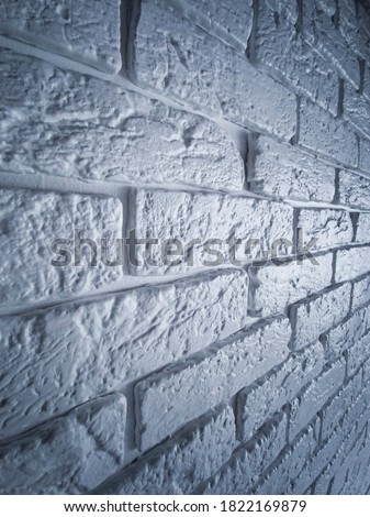 Fragment of a brick wall in perspective. Textured background. Neon glow effect on the wall. Decorative brick Bricks in perspective. Glowing brick wall. Uneven edge of a designer brick wall #1822169879