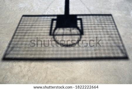 The shadow of a basketball hoop on a beach basketball court