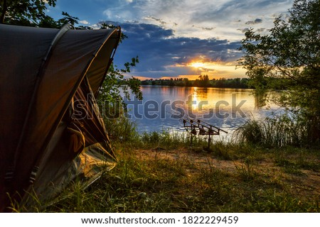 Fishing adventures, carp fishing. Angler, at sunset, is fishing with carpfishing technique. Camping on the shore of the lake.Carp Fishing Sunset Royalty-Free Stock Photo #1822229459