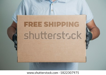 Detail of man with black gloves holding a cardboard box written free shipping to deliver products on gray background. Delivery concept. Delivery service concept. Copy space. Black friday concept. Royalty-Free Stock Photo #1822307975