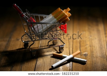 Cigarettes in shopping cart on wooden table on dark background Royalty-Free Stock Photo #182231210