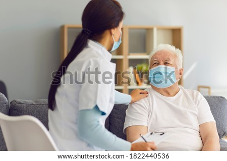 Caring female doctor supporting and cheering up senior male patient during home visit. Therapeutist and aged white-haired man, both wearing medical face masks, communicating and discussing treatment #1822440536