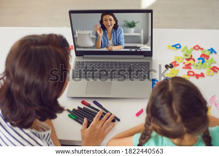 Mother and kid staying at home and E-learning via interactive private school platform. High angle back view mom and daughter video calling tutor on laptop or having online lesson with English teacher Royalty-Free Stock Photo #1822440563