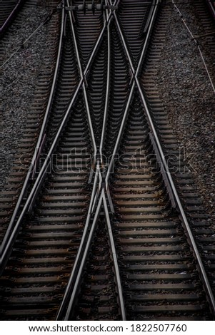 A clean picture of beautiful rail tracks coming together and splitting again.