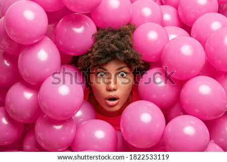 Nice looking surprised dark skinned woman stares with great surprisement at camera sticks out head through inflated pink balloons shocked how many guests came on party. Amazed ethnic birthday girl Royalty-Free Stock Photo #1822533119