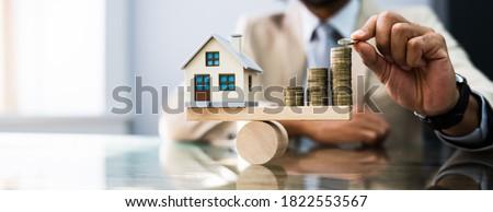 House Model Balance Equilibrium Concept. Real Estate Money Royalty-Free Stock Photo #1822553567