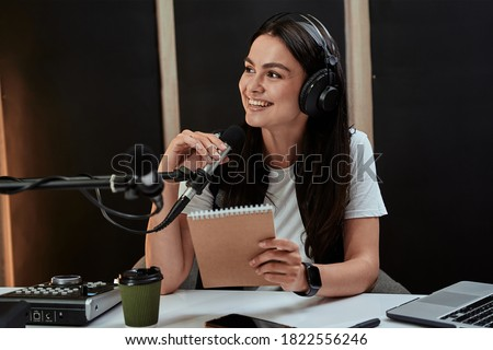 Portait of attractive young female radio host smiling aside while speaking in microphone, moderating a live show