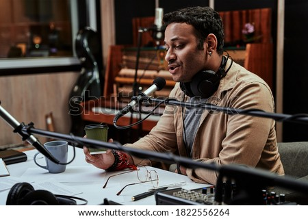 Portrait of young male radio host having a drink, looking focused while speaking in microphone, moderating a live show